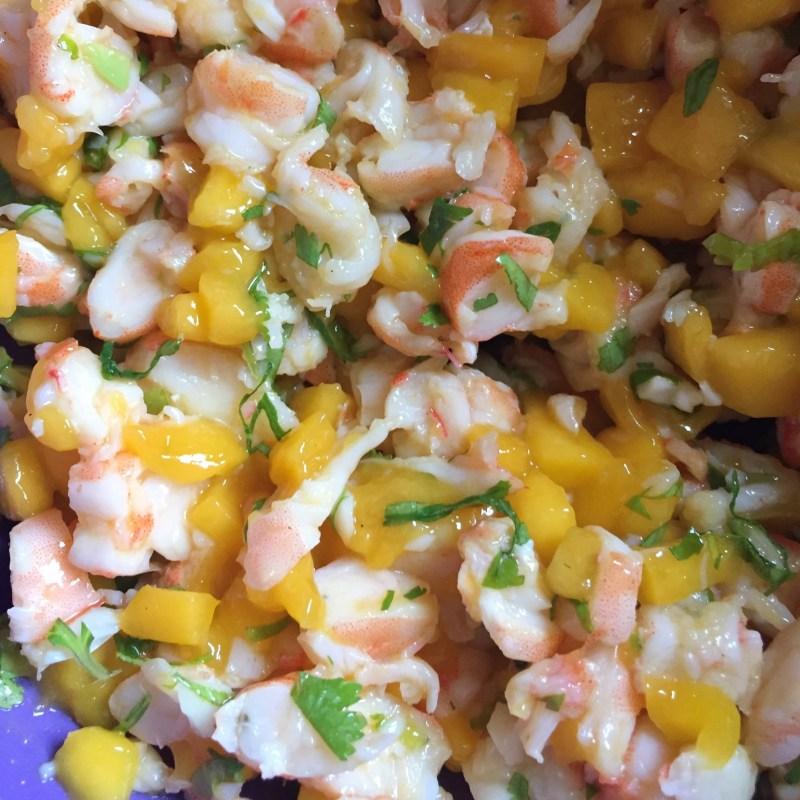 Préparation de crevettes et mangue en morceaux avec de la coriandre