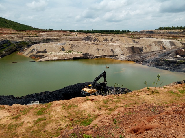 An excavator collects mined coal at the Maiganga coal mine