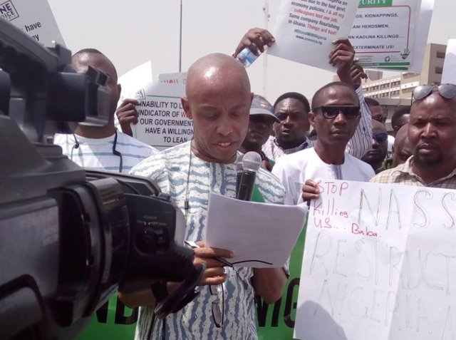 Former Executive Secretary of the NHRC, Chidi Odinkalu reads a speech during the 'I Stand With Nigeria' protest on Monday