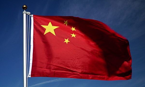 Stock 4K video clip footage of the Chinese flag flying outdoors in front of a blue sky. This is real video footage, not CGI.