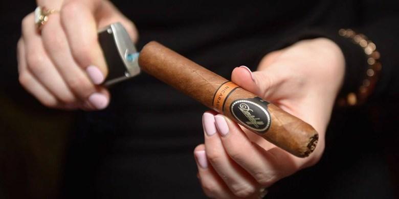 Woman lighting cigar The Blend Bar