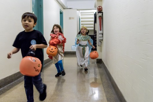 Children barrel down the hallway trick or treating in a building containing 110 apartments in the East Village, NYC. October 31st, 2016.