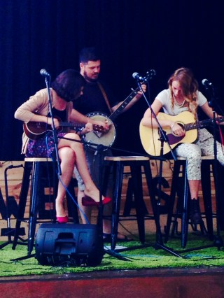 Catherine Ellis, Mr.Moore, and Brie Goetz performs on stage.