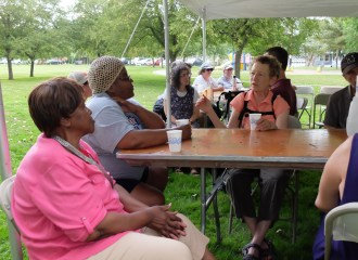 Community members from 2018 Building Unity event sitting under tent and talking