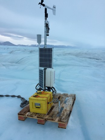 The Petermann data machine with batteries (yellow box), solar panels, electronics (white box), antenna, wind vane, and cables to ocean sensors on ground as last seen Aug.-2016.