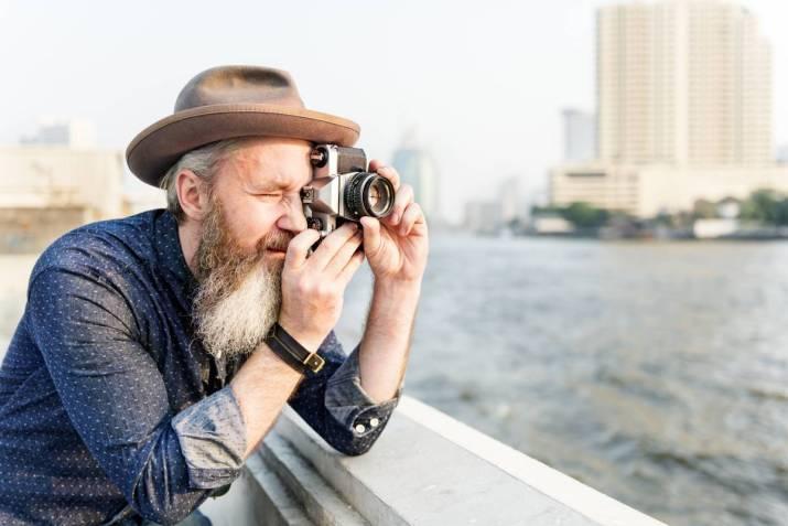 Senior man taking photographs.