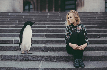 お互いを見ている女性とペンギン