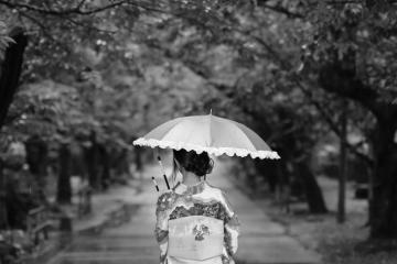 台風の中を歩く着物姿の女性