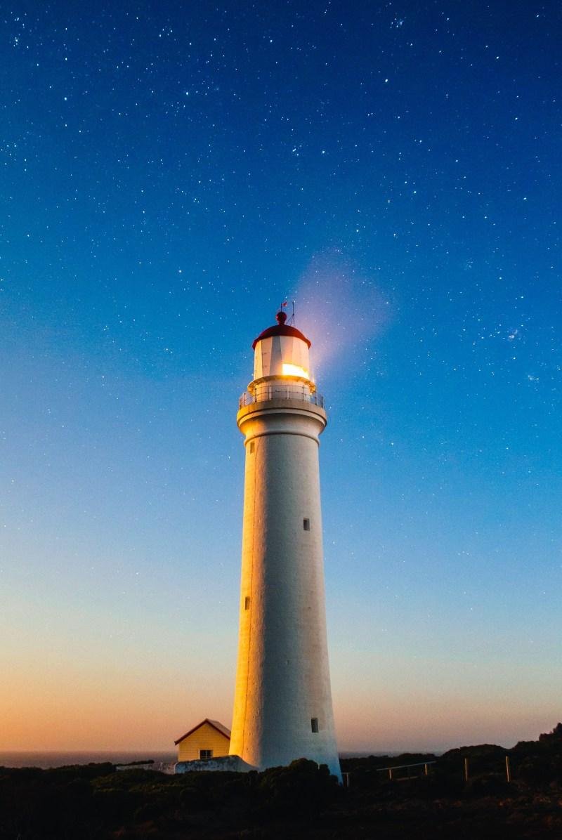 A beatiful photograph of a lighthouse at dusk.