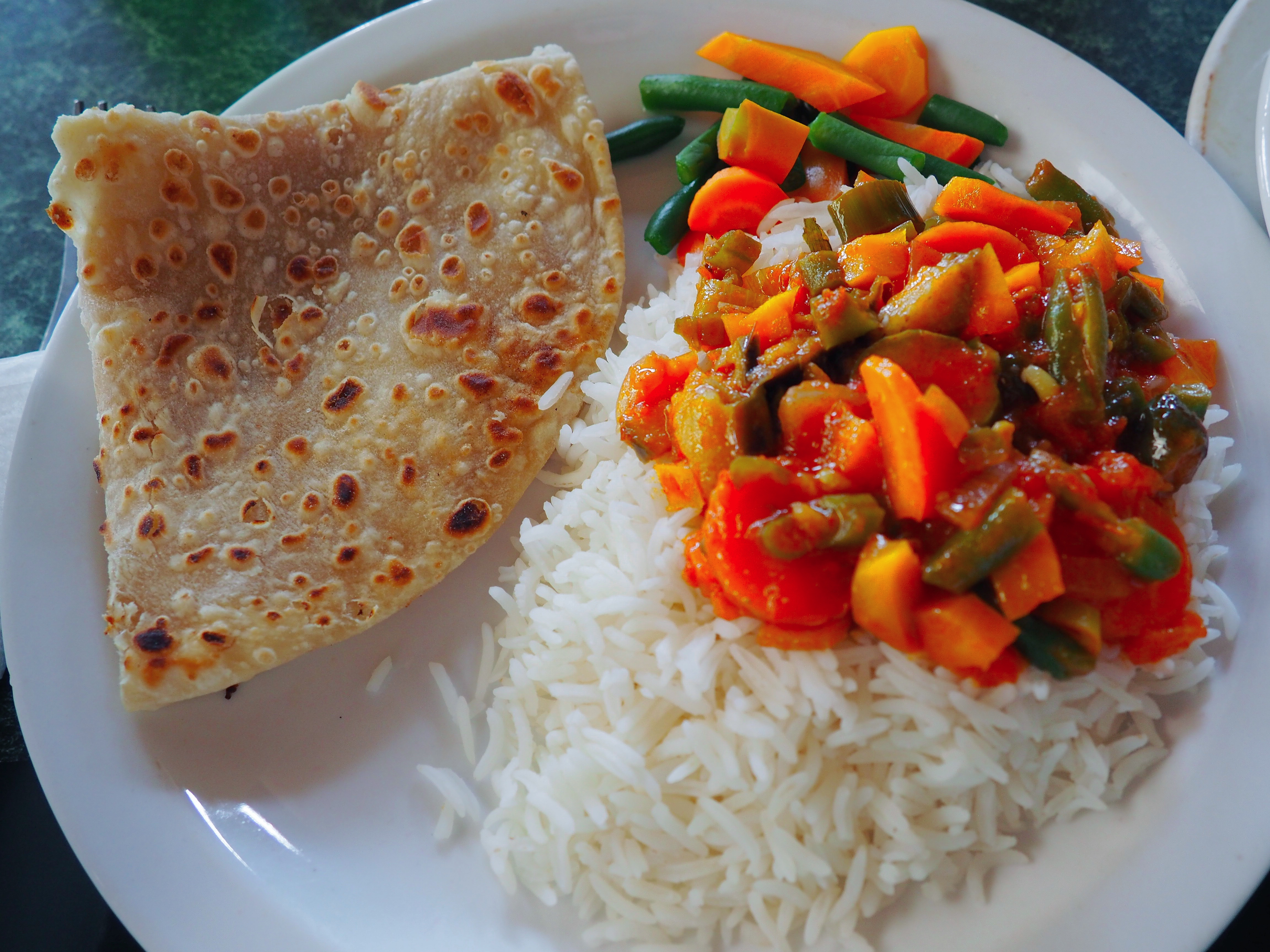 An out-of-focus Ugandan meal: vegetable stew, rice, and chapati