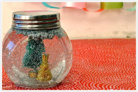 Tree and animal figurines with glitter inside a small glass jar