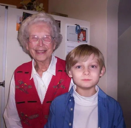 My grandmother standing with my son in front of a refrigerator.