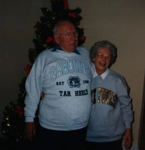 My grandmother and grandfather standing in front of a Christmas tree.