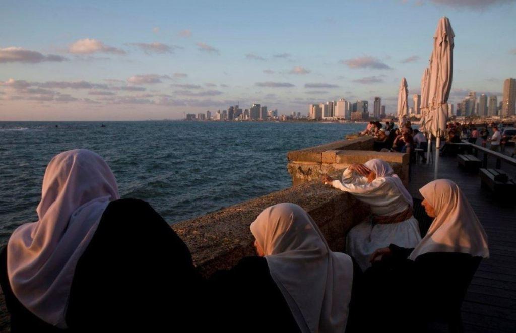 Femmes arabes regardnant le soleil couchant dans la ville Israelienne de Jaffa