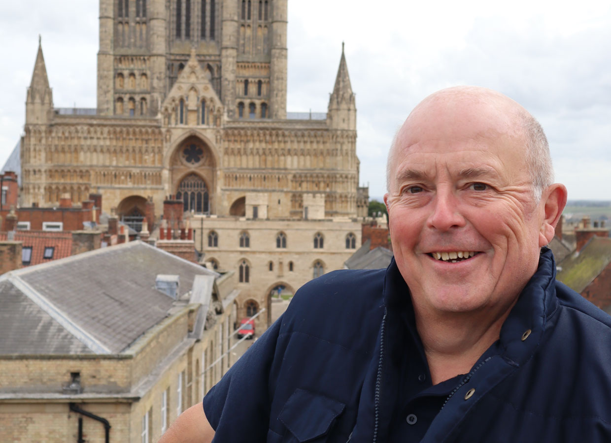 Mike Clay standing on caste walls in front of Lincoln Cathedral