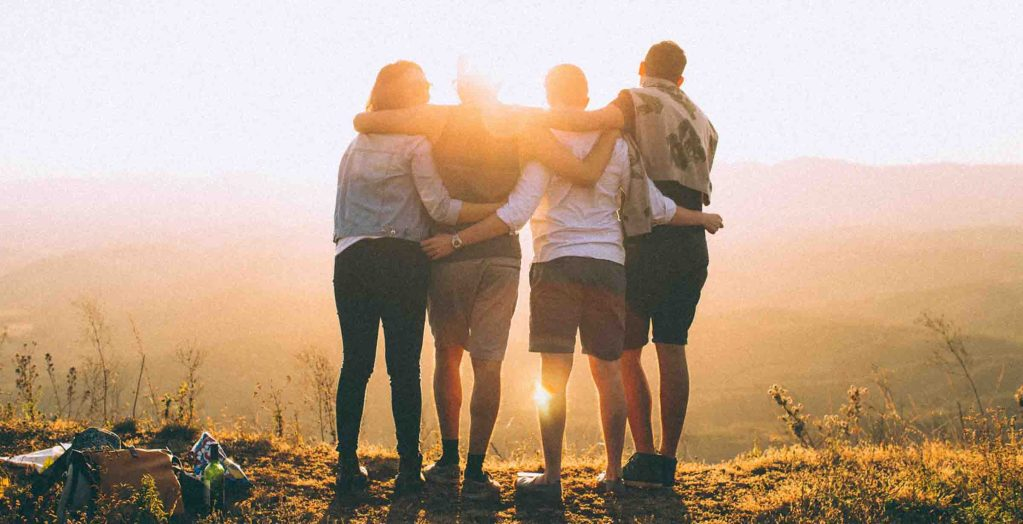 four friends standing on a hill looking at the sunset