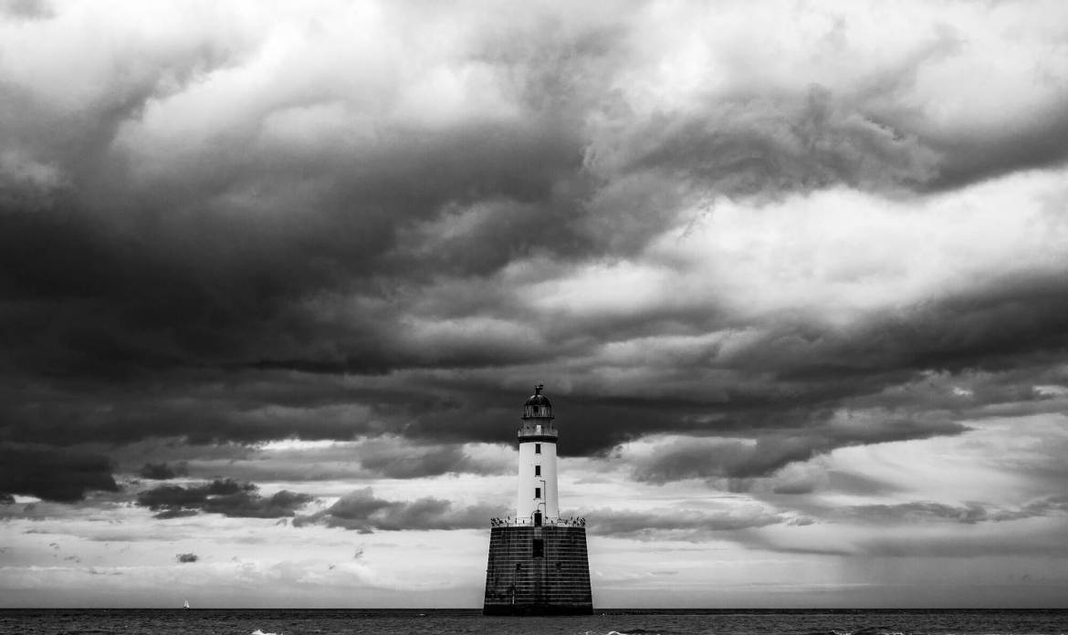 Lighthouse with a grey skyline behind it, to show how Zero Trust helps keep a watchful eye over those working in your organisational waters.