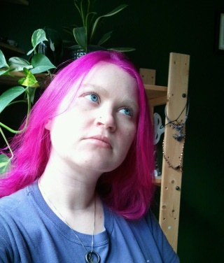 Image of Raechel Henderson looking up, her hair is pink and awesome.