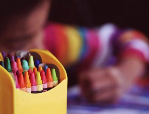 criança ao fundo pintando e a frente dela um porta lápis com muitos gizes de cera coloridos