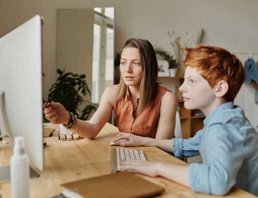 uma mulher mostrando para a criança algo na tela do computador