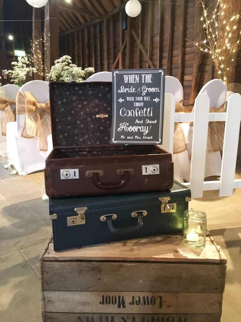 Suitcases filled with confetti and personalised signage rustic barn wedding inspiration