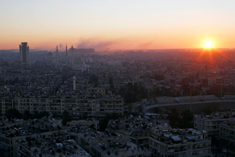 The sun rises while smoke is pictured near Aleppo's historic citadel, as seen from a government-controlled area of Aleppo