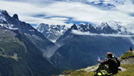 Man sitting down looking at French Alp peaks.