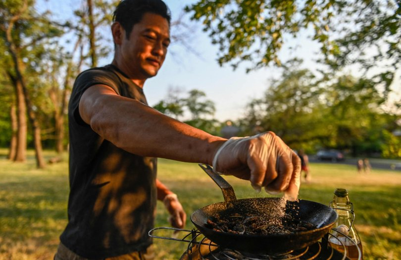 Chef Bun Lai seasons cicadas with salt as he fries them at Fort Totten Park in Washington, U.S., May 23, 2021. (AFP Photo)