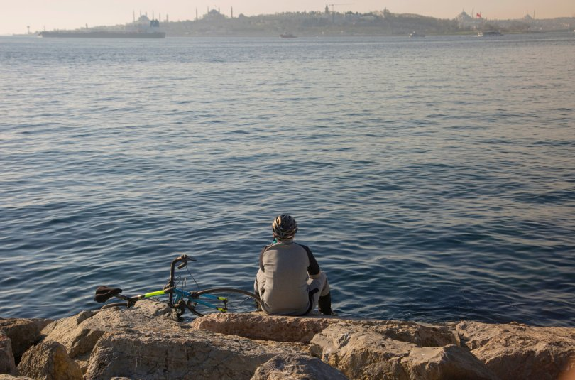 The back view of a sporty young man with a bicycle, looking at the view of the city of Istanbul, Turkey, Jan. 4, 2021. (Shutterstock Photo)
