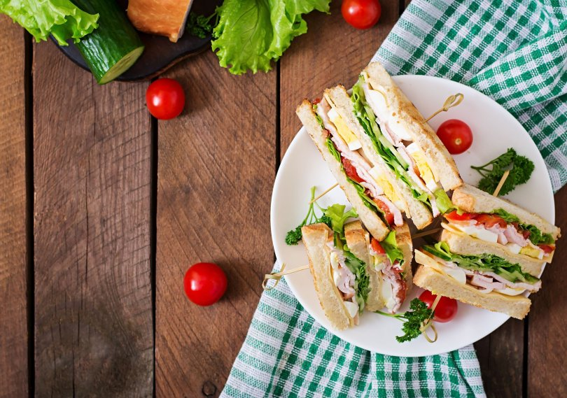 Club sandwich with cheese, cucumber, tomato, ham and eggs. (Shutterstock Photo)