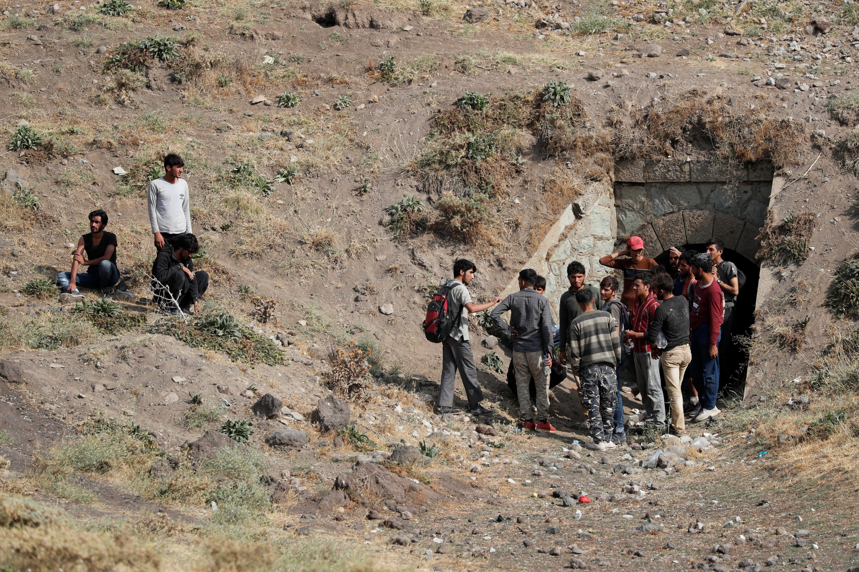Afghan migrants stand outside a tunnel under train tracks after crossing illegally into Turkey from Iran, as they hide from security forces near Tatvan in Bitlis province, Turkey, Aug. 23, 2021. (Reuters Photo)