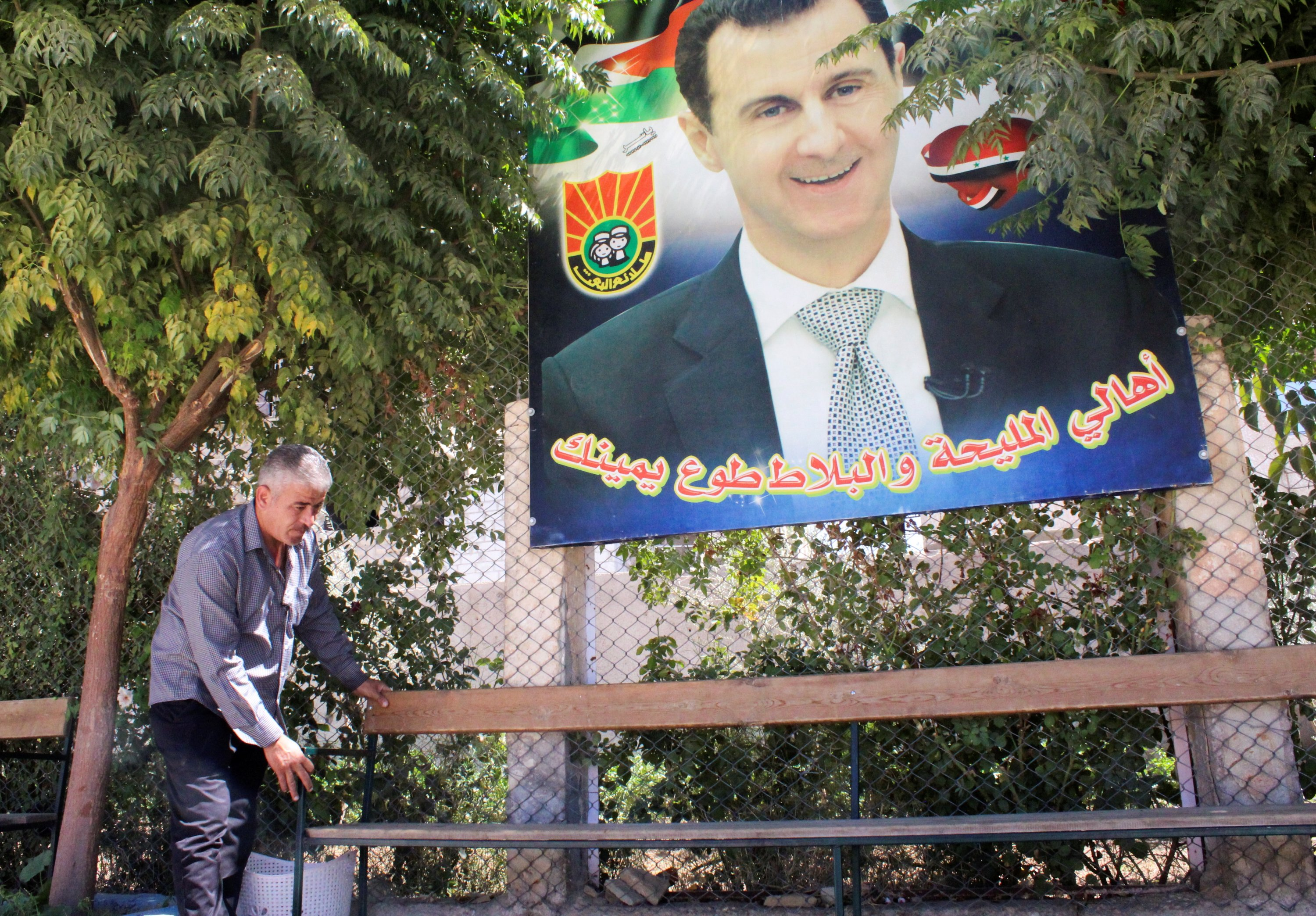 Mohamad Mazhar Doghmosh, a Syrian man who helps in the restoration of Mleiha rural school, adjusts a bench near a poster depicting Syria's President Bashar al-Assad, in Mleiha, Syria, Sept. 14, 2021. (Reuters Photo)