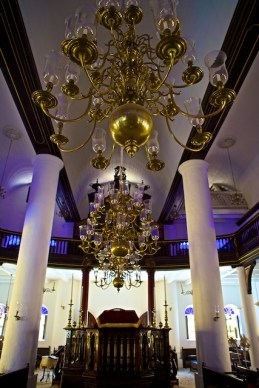 Inside the Mikvé Israel Emanuel Synagogue in Willemstad, Curaçao, sunlight, filtered through dozens of cobalt blue stained-glass windows, splashed the sills, white walls, mahogany benches, and white sand-coverd floor with a heavenly blue hue.