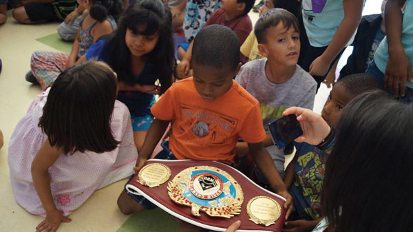 "courtesy photo/boys & girls club redlands Children at the Boys & Girls Club in Redlands check out undefeated super lightweight boxer Miguel Angel ""Mikey"" Garcia's belt. Garcia spoke to children about never giving up and staying in school."