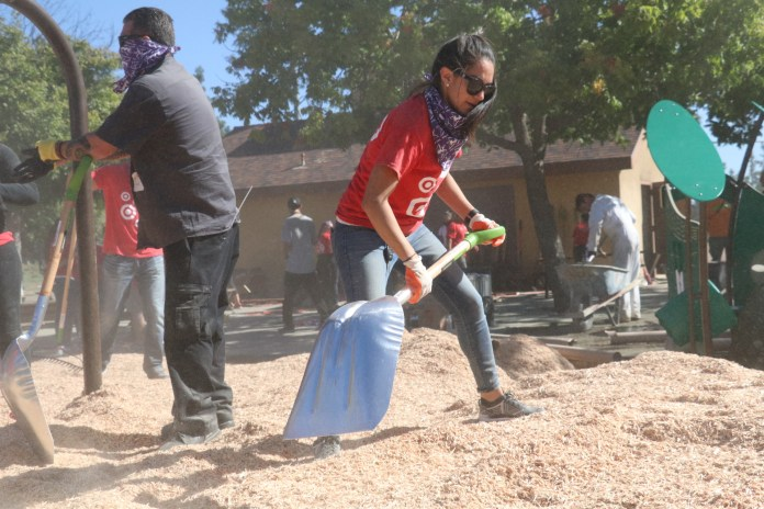 Photo/Anthony Victoria: Target associate Deanna Flores helping shovel wood chips inside the new playground area at Seccombe Lake Park.
