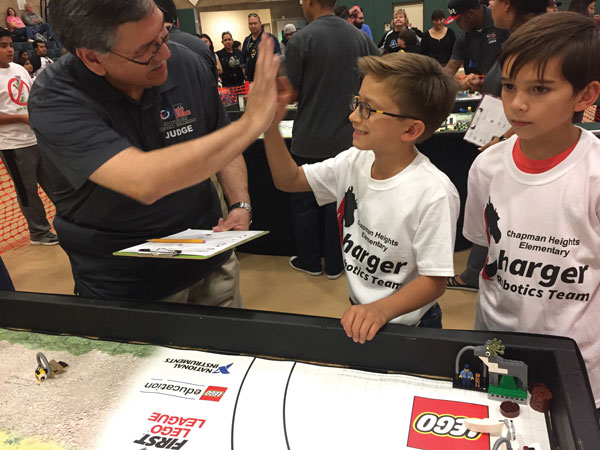 iecn photo/yazmin alvarez  Rialto School Board member Joe Martinez high fives Rhett Bogh, 10, as he completes a mission during the First Lego League Rialto qualifying tournament Nov. 12 at Rialto Middle School.