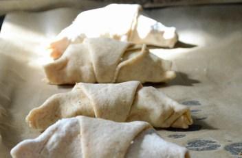 La hornene etterheve under plastfolie. Hornene blir ekstra fine om du pensler dem med et sammenvispet egg og drysser sesamfrø over.
