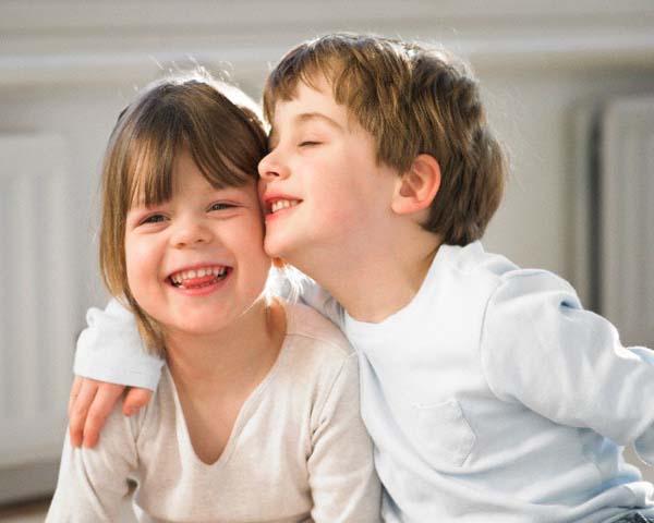 28 Dec 2004 --- Smiling children hugging indoors --- Image by © Adrian Weinbrecht/cultura/Corbis