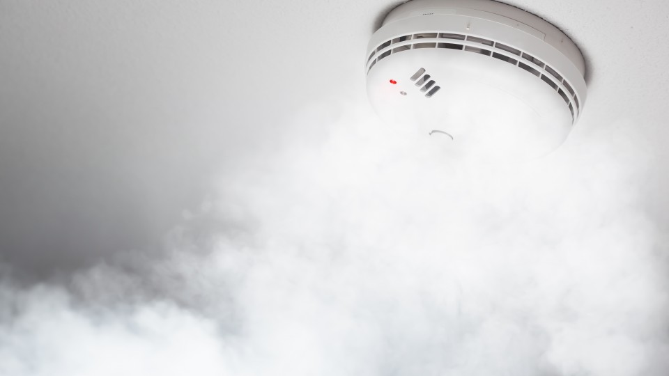 smoke detector of fire alarm in action, white background