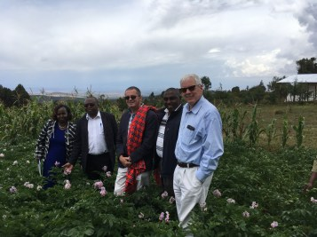 Potato farm owner, Robert Kamau (second from right), supplies potatoes to New Holland Chips. Observing Mr. Kamau's potato field are (from left to right) Nancy Kahare, sub-county agriculture officer; Robert Thuo, county minister of agriculture; Ambassador Vincent O'Neill; Mr. Kamau; and Scott Angle.