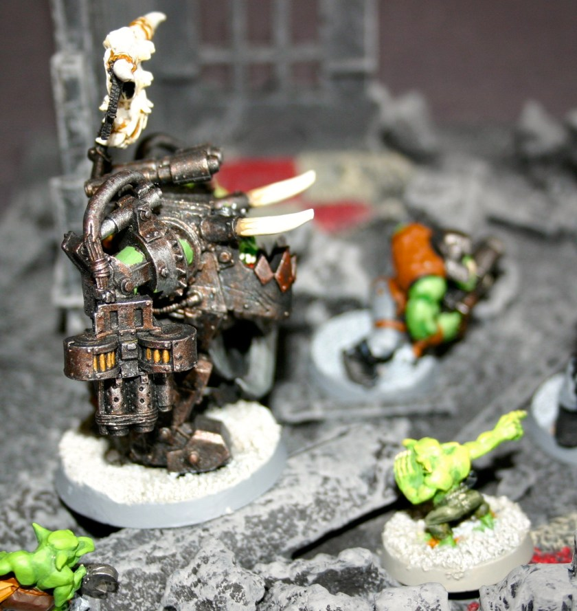 Ork Warboss in Mega-Armour from Felix's collection in the ruins of an Imperial City.