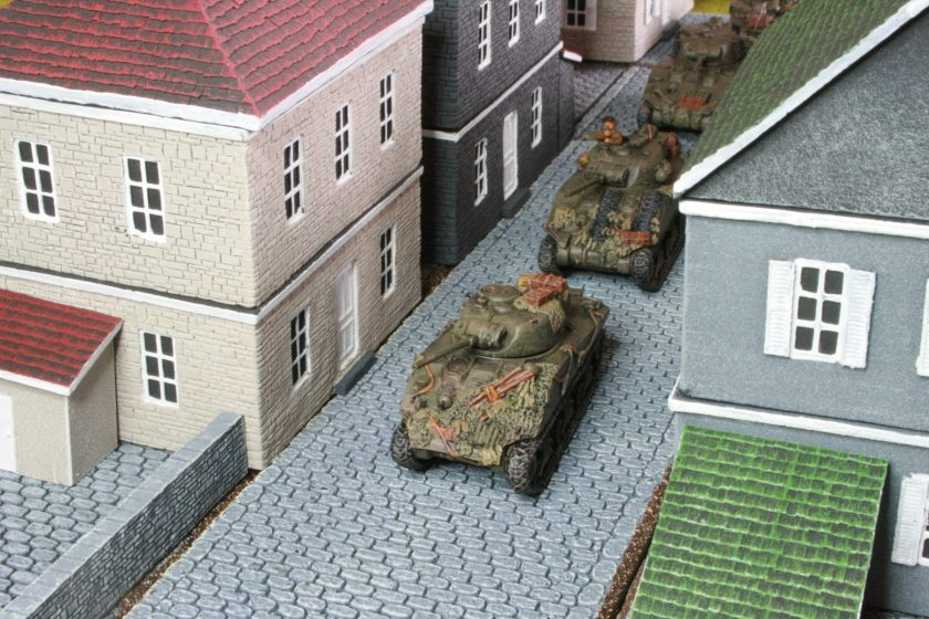 British Shermans in column moving down a cobbled street in Normandy. Roads and buildings are from Battlefront.