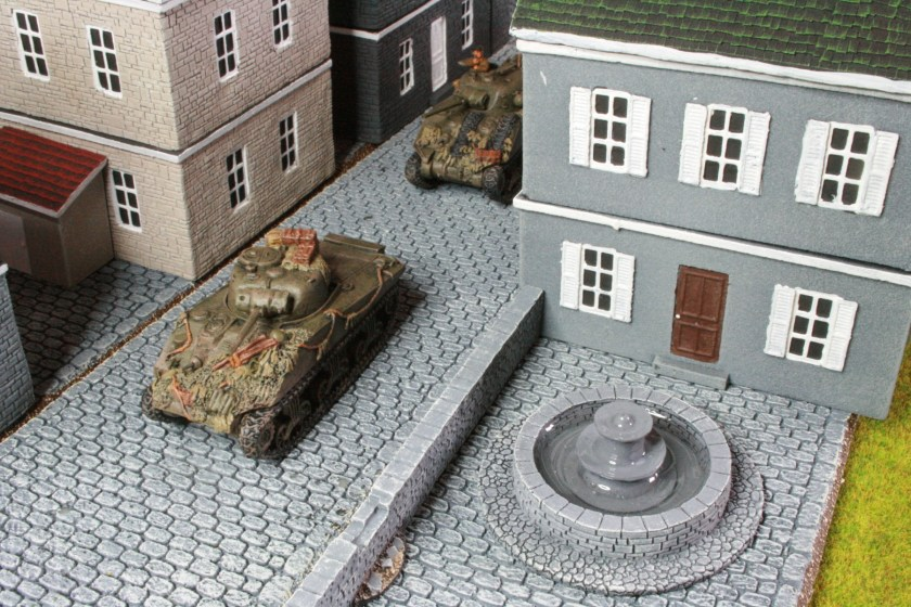 British Shermans, pass by a fountain in Normandy. The fountain, roads and buildings are from Battlefront.