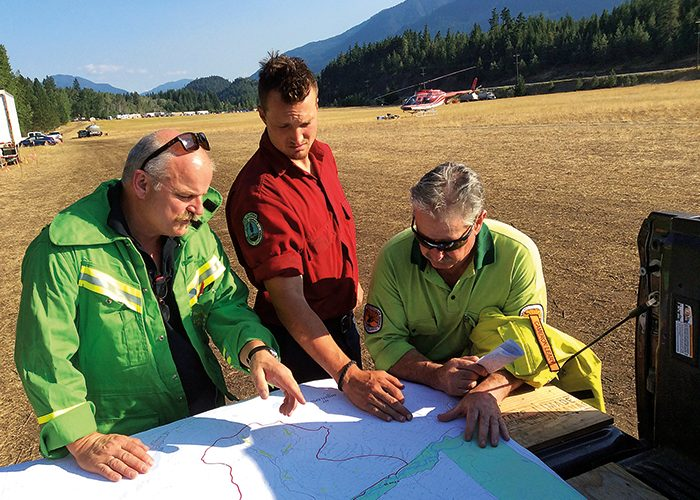 Alistair Drayton Australian IC and Cameron Leary Australian Operations Section Chief are discussing control options with Dan Dykens, British Columbia Forest Service on the Cougar Creek Fire 247 in 2015.