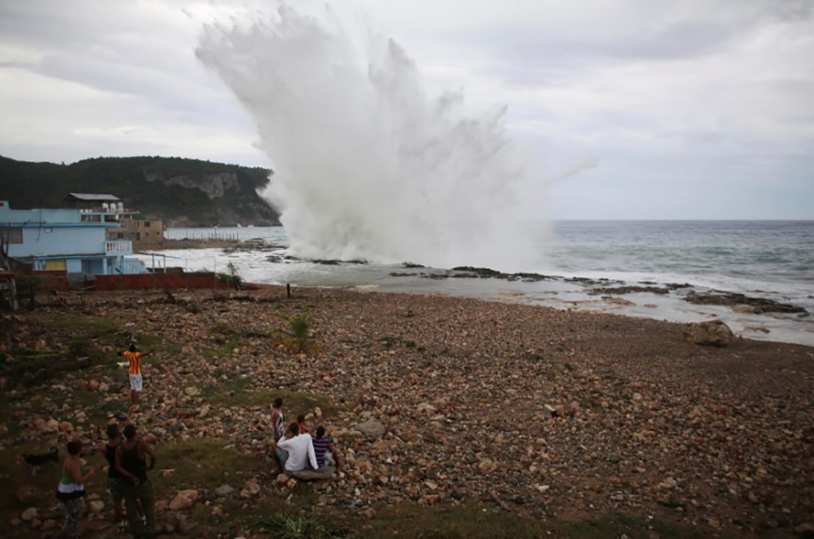 People watch waves splashing on the beach at Siboney ahead of the arrival of Hurricane Matthew in Cuba, October 4, 2016. REUTERS/Alexandre Meneghini