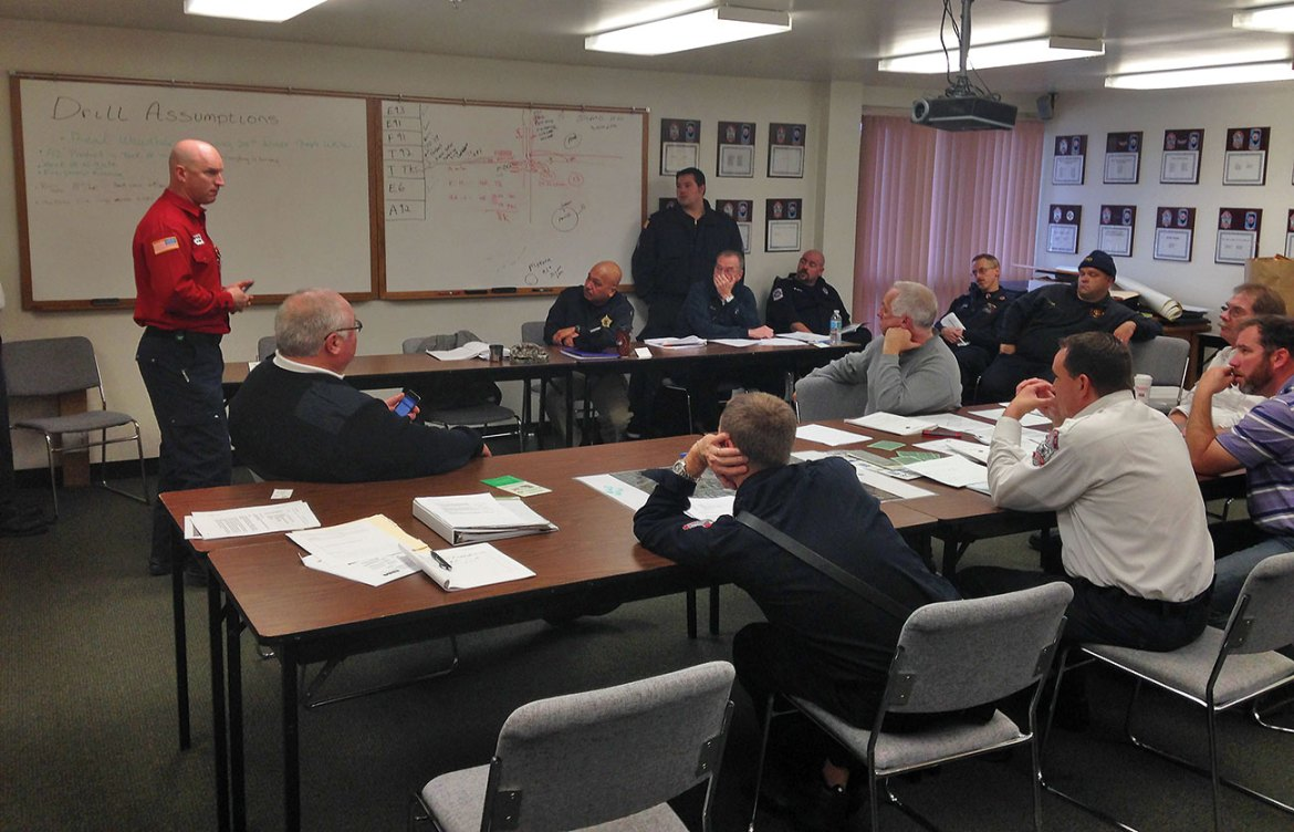 A group of Emergency Responders gather to review pre-plans for storage-tank emergencies.