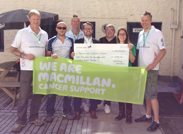Neil (far right) and Mark (second left) can be seen with other members of the team and sponsors handing the cheque over to Genevieve Drinkwater from Macmillan Cancer Support.