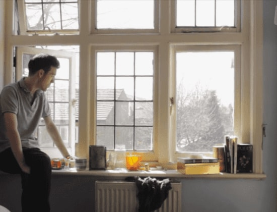 A still of a man sitting by an open window, looking outward, taking from Coming Out Of The West, an LGBT+ short films