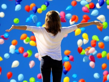 Lady walking through balloons with arms stretched out