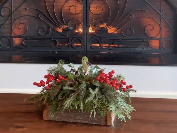Decorative box with natural boughs in front of fireplace